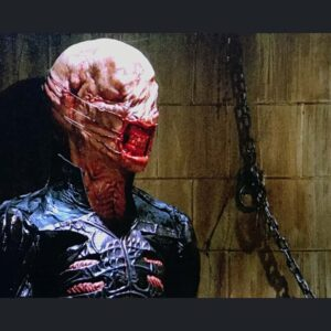 Mid shot of actor wearing Chatterer prosthetic makeup, 3/4 profile. Bald and deformed head, eyes sewn shut with lips pulled back by fish hooks on wires.