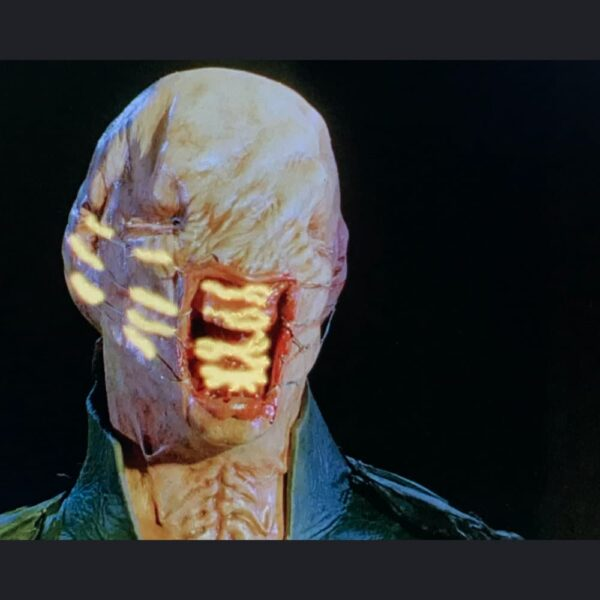 Chatterer prosthetic makeup. Mouth open with yellow streams of light around face. Bald and deformed head, eyes sewn shut with lips pulled back by fish hooks on wires.