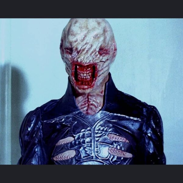 Mid shot of actor wearing Chatterer prosthetic makeup. Bald and deformed head, eyes sewn shut with lips pulled back by fish hooks on wires.