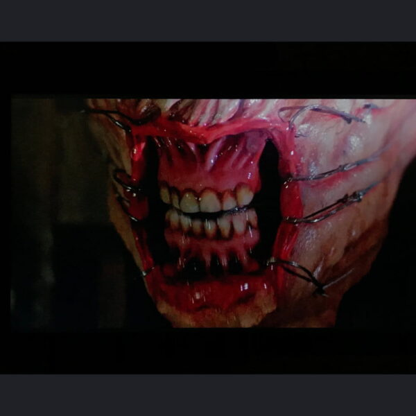 Extreme close up of prosthetic makeup teeth with lips pulled back by fish hooks