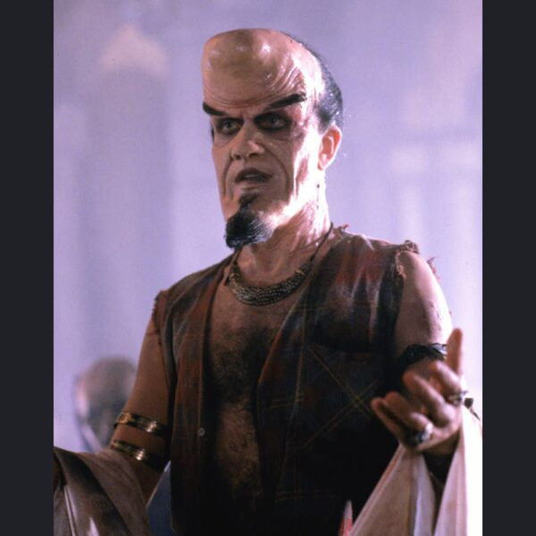 Mid shot of actor wearing crescent moon faced prosthetic makeup.